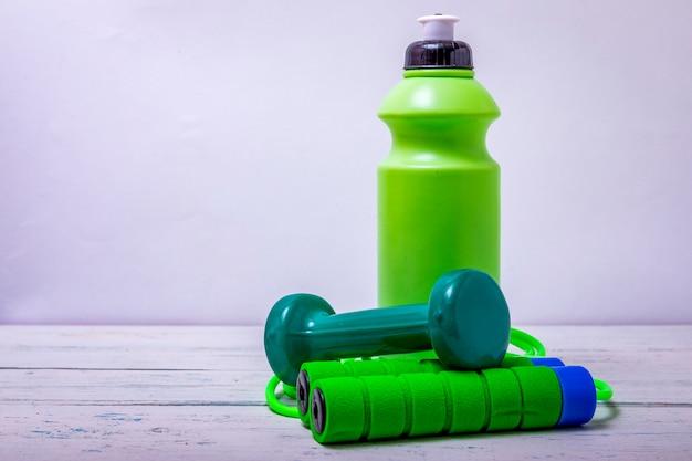 緑の色、コピースペースを持つ健康的なライフスタイルのコンセプトのスポーツ機器の正面図。