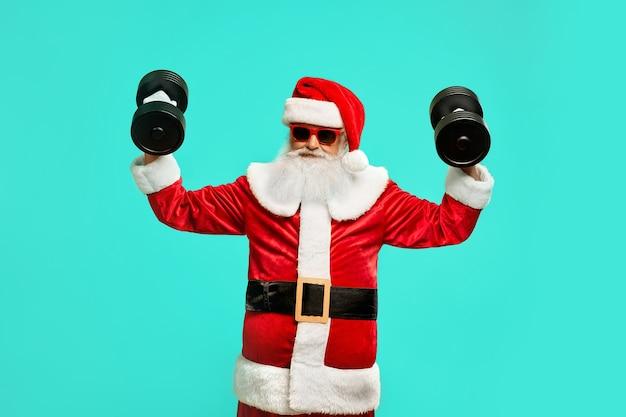 Dumbbels를 들고 낚시를 좋아하는 산타 클로스의 전면 모습입니다. 크리스마스 의상에서 재미있는 수석 남자의 고립 된 초상화
