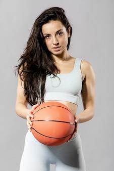 バスケットボールのボールでスポーティな女性の正面図