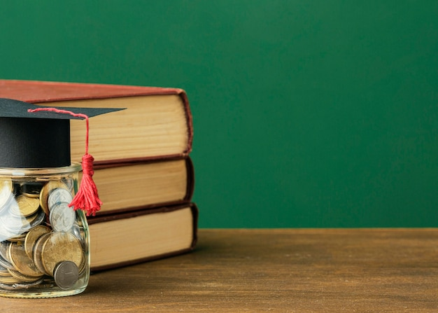 Вид спереди стопки книг с копией пространства и банкой монет