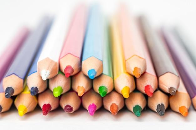 Вид спереди сложенных цветных карандашей на белом фоне