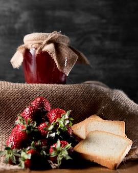 Вид спереди клубничного варенья в банке с хлебом