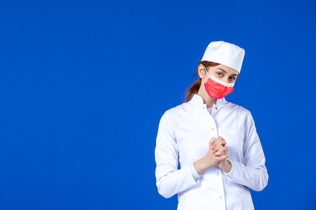 青に赤いマスクと医療スーツでストレスを感じた若い看護師の正面図