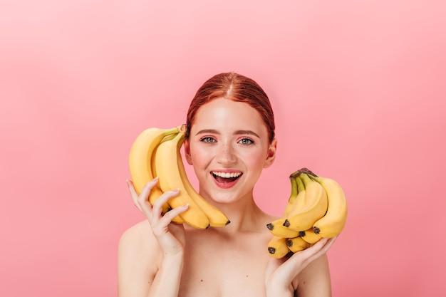 바나나와 함께 멋진 생강 소녀의 전면 모습입니다. 분홍색 배경에 열대 과일을 들고 행복 누드 여자의 스튜디오 샷.