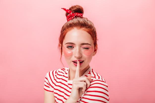 손가락으로 입술을 만지고 눈 패치와 함께 멋진 젊은 여자의 전면 모습. 스킨 케어 치료를 하 고 비밀 기호를 보여주는 사랑스러운 소녀의 스튜디오 샷.