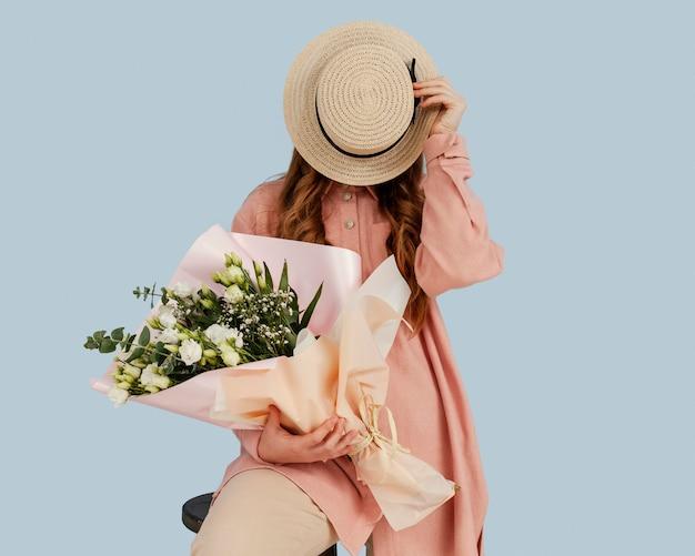 春の花の花束でポーズをとってスタイリッシュな女性の正面図