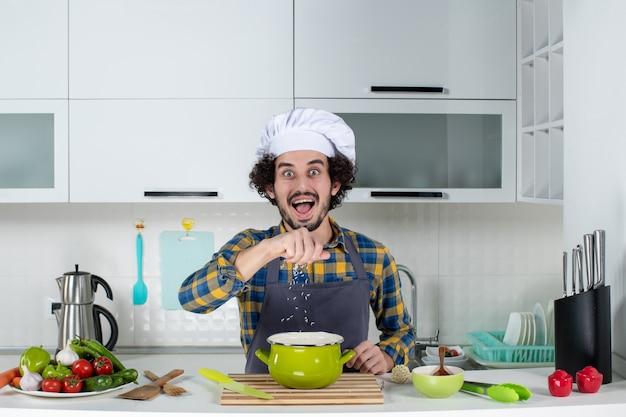 白いキッチンで鍋に塩を追加する新鮮な野菜と驚いたシェフの正面図