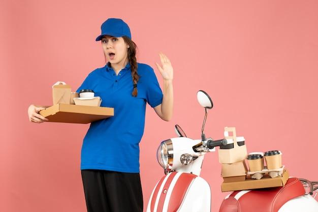 パステル ピーチ色の背景にコーヒーと小さなケーキを保持しているオートバイの隣に立っている驚いた宅配便の女の子の正面図