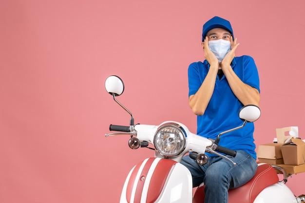 パステル調の桃の背景に注文を配達するスクーターに座っている帽子をかぶった医療マスクを着た驚いた宅配便の男性の正面図