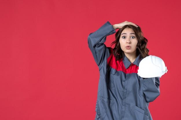 단단한 모자를 들고 격리된 빨간색 배경에 머리에 손을 얹은 놀란 여성 건축가의 전면
