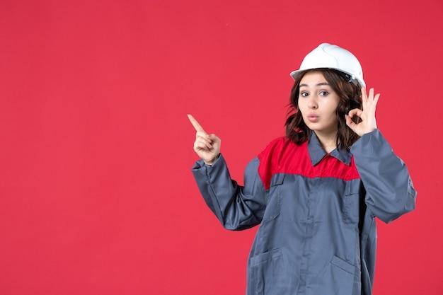 모자를 쓴 제복을 입은 놀란 여성 건축업자의 전면 모습과 격리된 빨간색 배경을 가리키는 안경 제스처