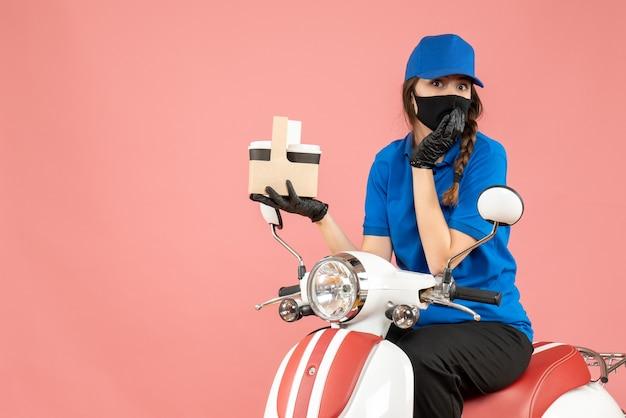 医療用マスクと手袋を着て、パステル調の桃の背景に注文を配達するスクーターに座っている驚く女性配達員の正面図