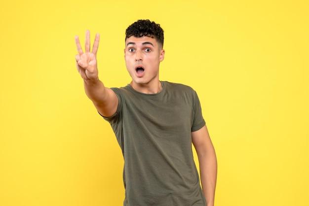 Вид спереди удивленного парня показывает три пальца