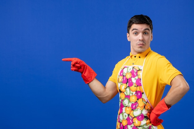 파란 벽에 서 있는 허리에 손을 얹고 앞치마를 입은 놀란 남성 가사도우미의 전면 모습