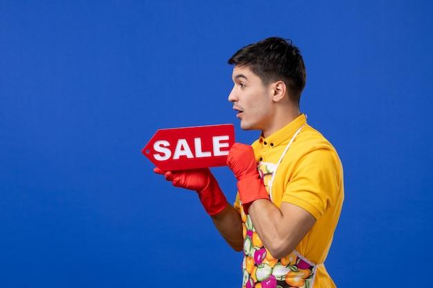 파란색 외진 벽에 판매 표지판을 들고 노란색 티셔츠를 입은 놀란 남성 가정부의 전면