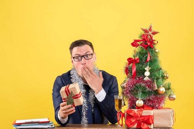 Вид спереди удивленного мужчины, держащего подарок, сидящего за столом возле рождественской елки и подарков на желтом