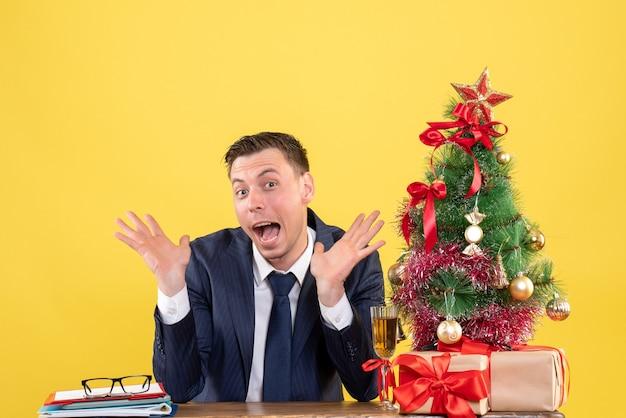 크리스마스 트리와 선물 근처 테이블에 앉아 그의 입을 열고 열린 손으로 놀란 남자의 전면보기