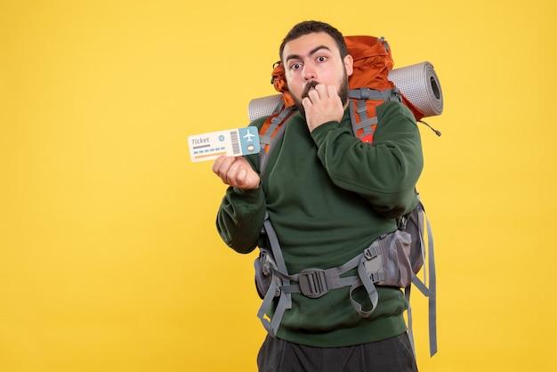 黄色い背景に何かに集中したバックパックを持つ驚いた旅行者の男の正面図