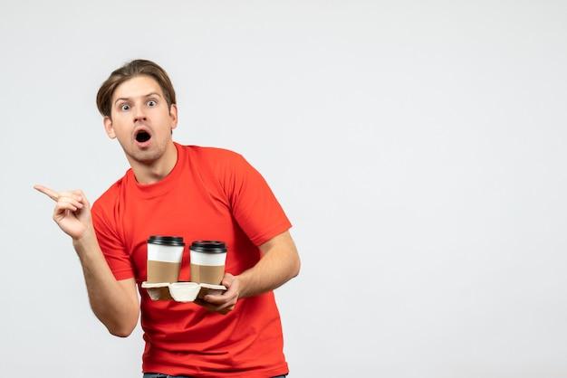 紙コップでコーヒーを保持し、白い背景の右側に何かを指している赤いブラウスで驚いた若い男の正面図