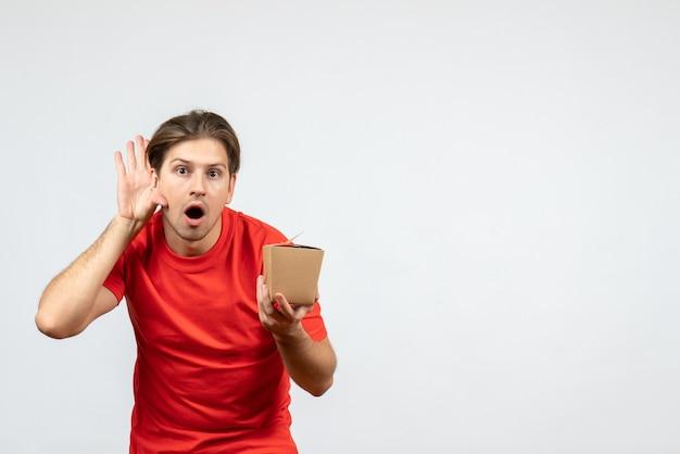 小さな箱を保持し、白い背景で最後のうわさ話を聞いている赤いブラウスで驚いた若い男の正面図