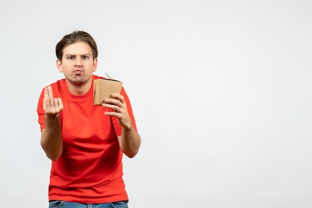 白い背景の上の小さなボックスを保持している赤いブラウスで驚いた若い男の正面図