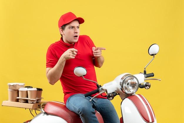 黄色の背景に上向きの注文を配信赤いブラウスと帽子を身に着けている驚いた若い男の正面図