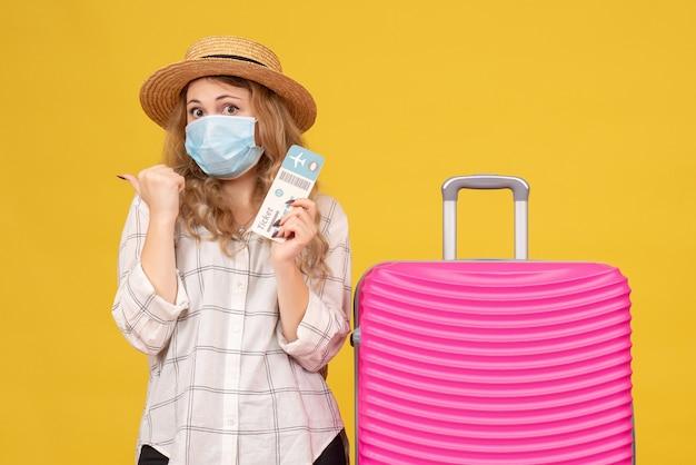 Вид спереди удивленной молодой леди в маске, показывающей билет и стоящей рядом со своей розовой сумкой, указывающей на желтый