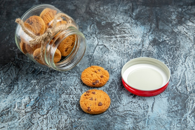 暗い表面のガラス缶の中の甘いクッキーの正面図