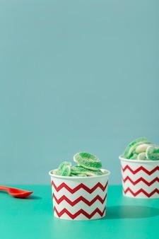 Вид спереди сладкого желе в чашках с ложкой и копией пространства