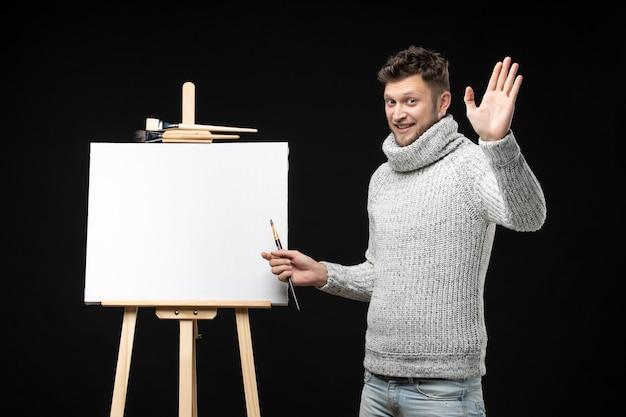 검정에 5를 보여주는 감정적인 표정을 가진 재능 있는 남성 화가의 전면