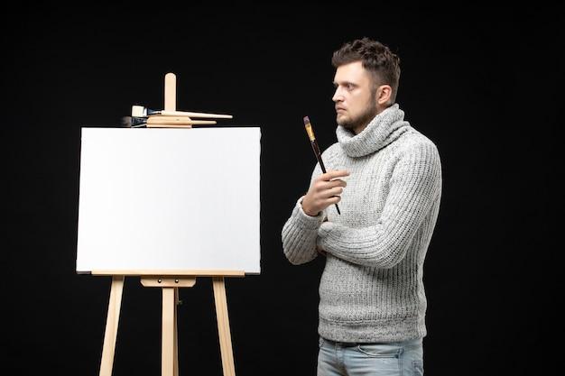 재능 있는 사려깊은 남성 예술가의 전면 뷰는 검정색에 집중되어 있습니다.