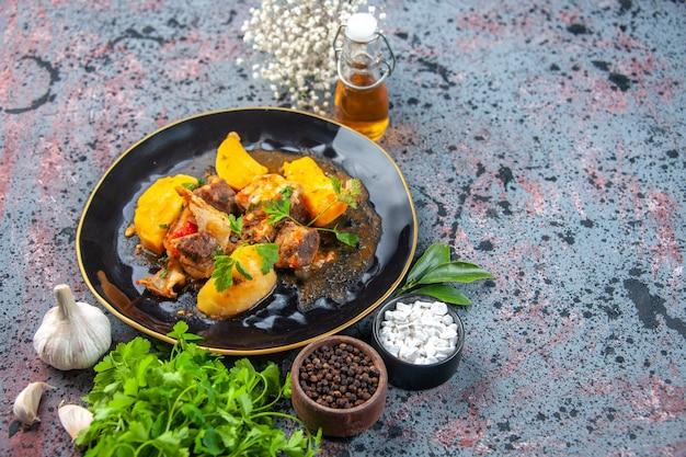 Вид спереди вкусного ужина с мясным картофелем, подаваемым с зеленью в черной тарелке и бутылке чесночного масла со специями
