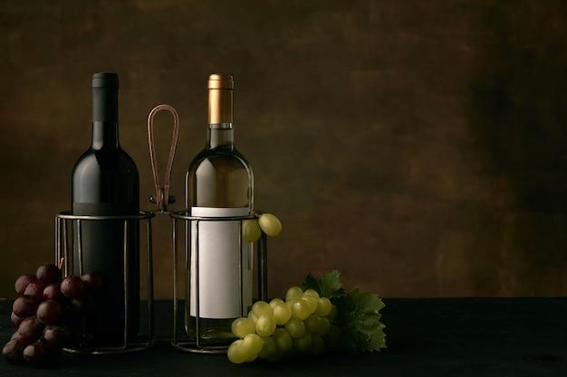 어두운 스튜디오 배경에 와인 병 포도의 맛있는 과일 접시의 전면 뷰, 텍스트 또는 이미지를 삽입 할 공간을 복사합니다. 맛있는 음식과 음료.