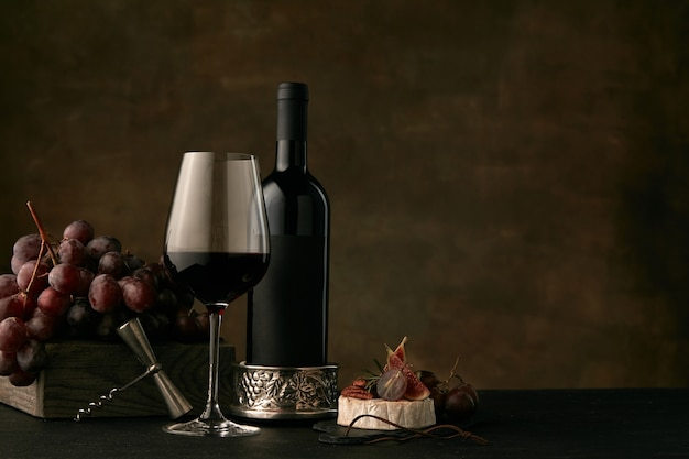 暗いスタジオの背景にワインボトルとおいしいフルーツプレートの正面図
