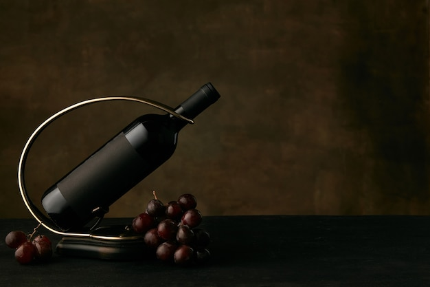 暗闇の中でワインボトルとブドウのおいしいブドウプレートの正面図