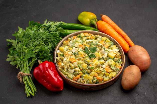 暗い表面に緑と野菜のおいしいサラダの正面図