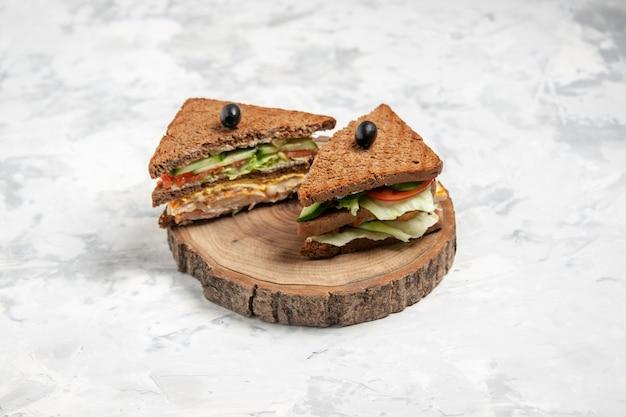 空きスペースのあるステンド グラスの白い表面に木のまな板にオリーブで飾られた黒パンのおいしいサンドイッチの正面図