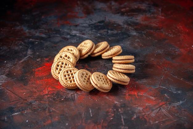 여유 공간이 있는 혼합 색상 배경에 둥근 형태로 배열된 맛있는 설탕 쿠키의 전면 보기