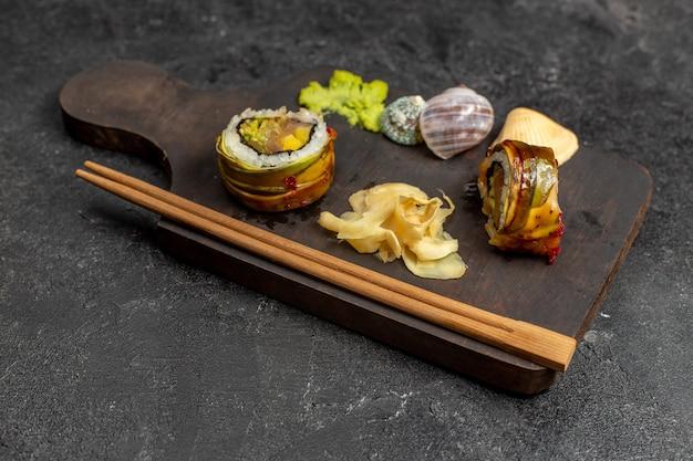 Вид спереди вкусных суши, нарезанных рыбных рулетов с зеленым васаби и палочками на серой стене