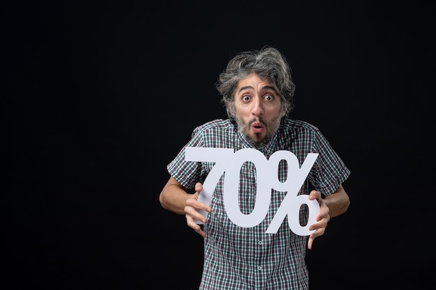 Вид спереди испуганного человека, держащего знак на черной стене