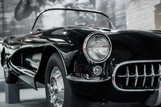 黒い車の正面図。自動車展示会に立っている高級車の束の屋内