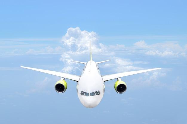 Вид спереди пассажирского самолета на голубом небе.