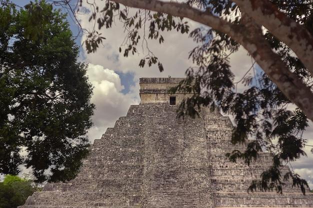 いくつかの木でろ過されたメキシコのチチェンイツァ考古学複合施設のピラミッドの先端の正面図