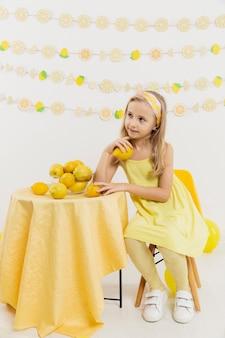レモンを押しながらポーズをとって考える女の子の正面図