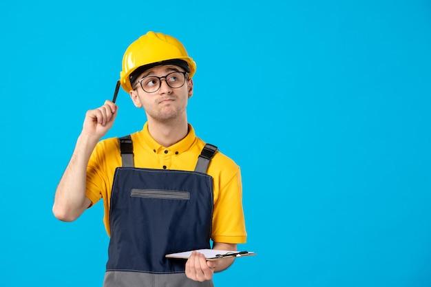 青の彼の手でファイルノートと制服を着た思考の男性ビルダーの正面図