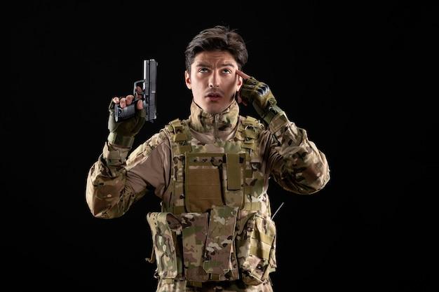 총 검은 벽을 들고 제복을 입은 생각하는 군인의 전면 보기