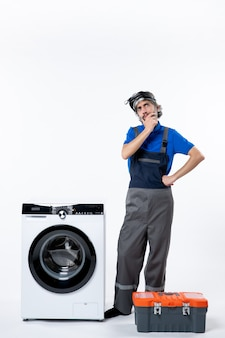 白い壁に洗濯機ツールバッグの近くに立っている思考修理工の正面図