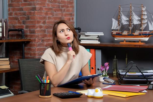 オフィスの机に座っている蛍光ペンを保持している思考の女性の正面図