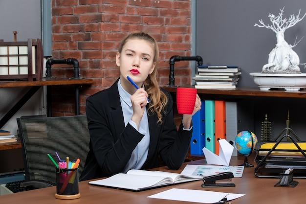 책상에 앉아 사무실에서 빨간 컵을 들고 생각하는 젊은 여성의 전면 보기
