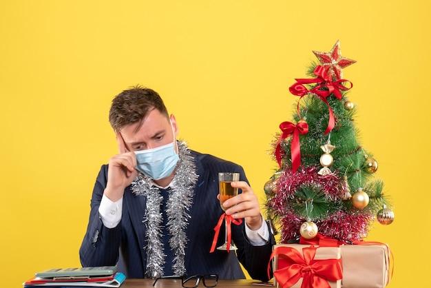 Вид спереди вдумчивого делового человека, держащего шампанское, сидящего за столом возле рождественской елки и подарков на желтом